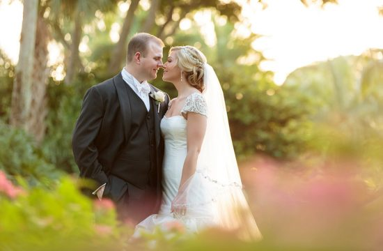 A bride, wearing a cap sleeve dress, kisses her husband on the front lawn at the Breakers in Palm Beach.