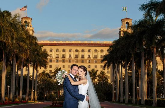 The front of the Breakers Hotel serves as a backdrop for wedding portraits in Palm Beach.