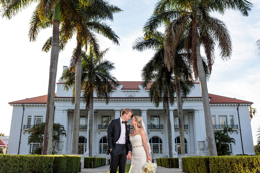 A couple pose for a wedding portrait on the front of the Flagler Museum before their Palm Beach Wedding.