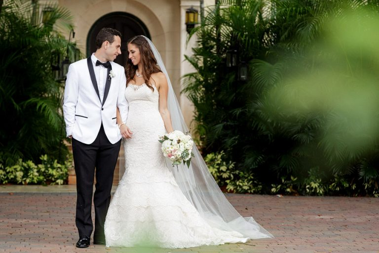 A bride, wearing a lace dress, poses with her groom in a white tuxedo jacket at Villa Woodbine in Coconut Grove before their ceremony.
