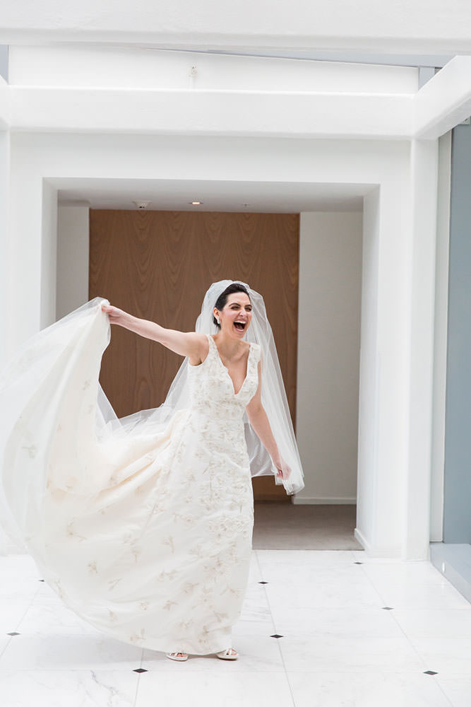 Bride laughing as she twirls around the Miami Beach Edition