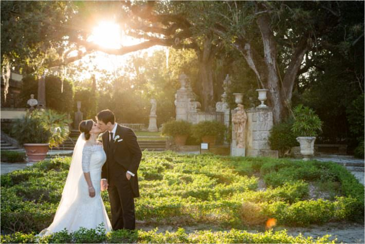Bride and groom in the gardens at Vizcaya during their wedding day.