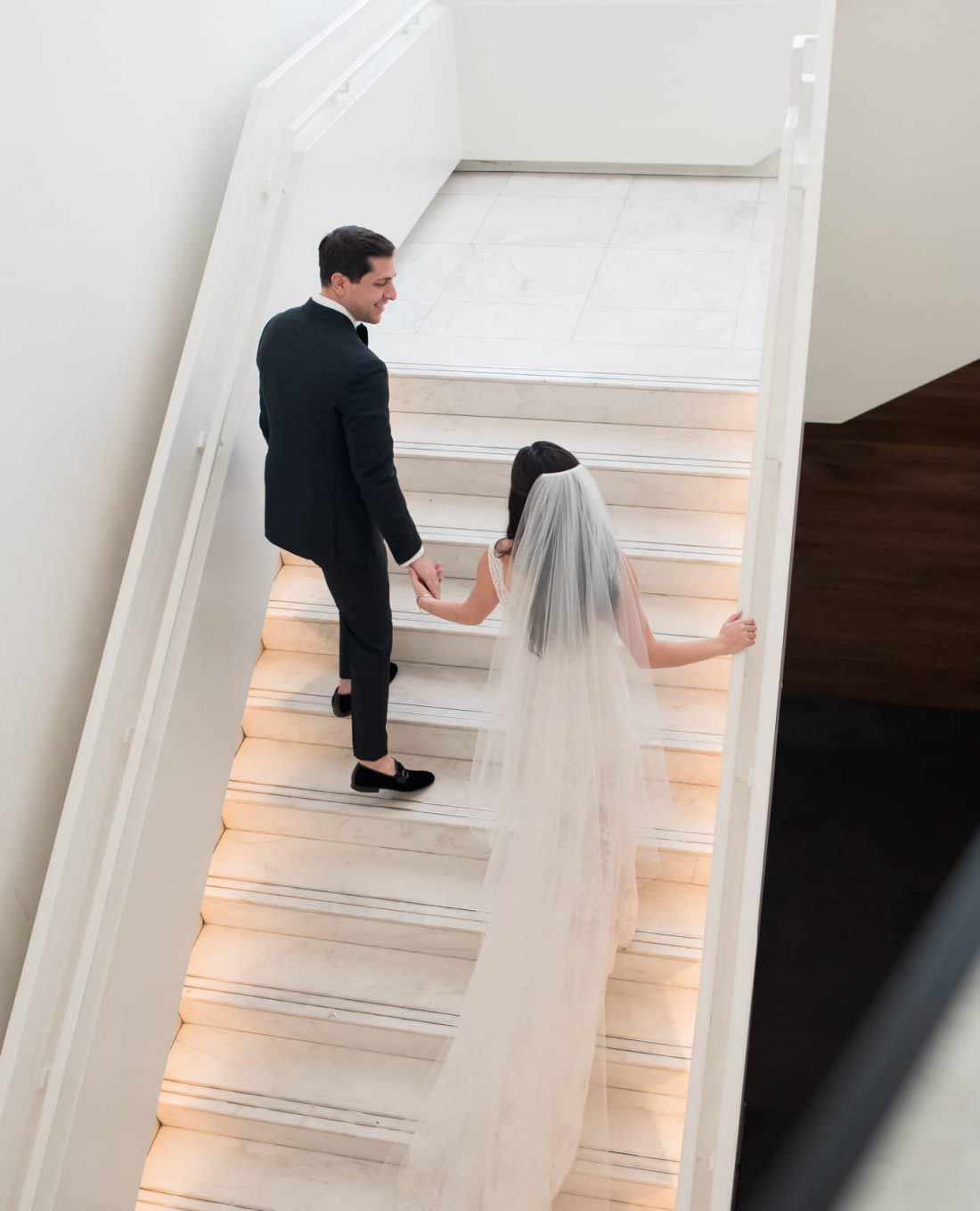 Bride and groom walk up the stairs hand in hand at the Miami Beach Edition.