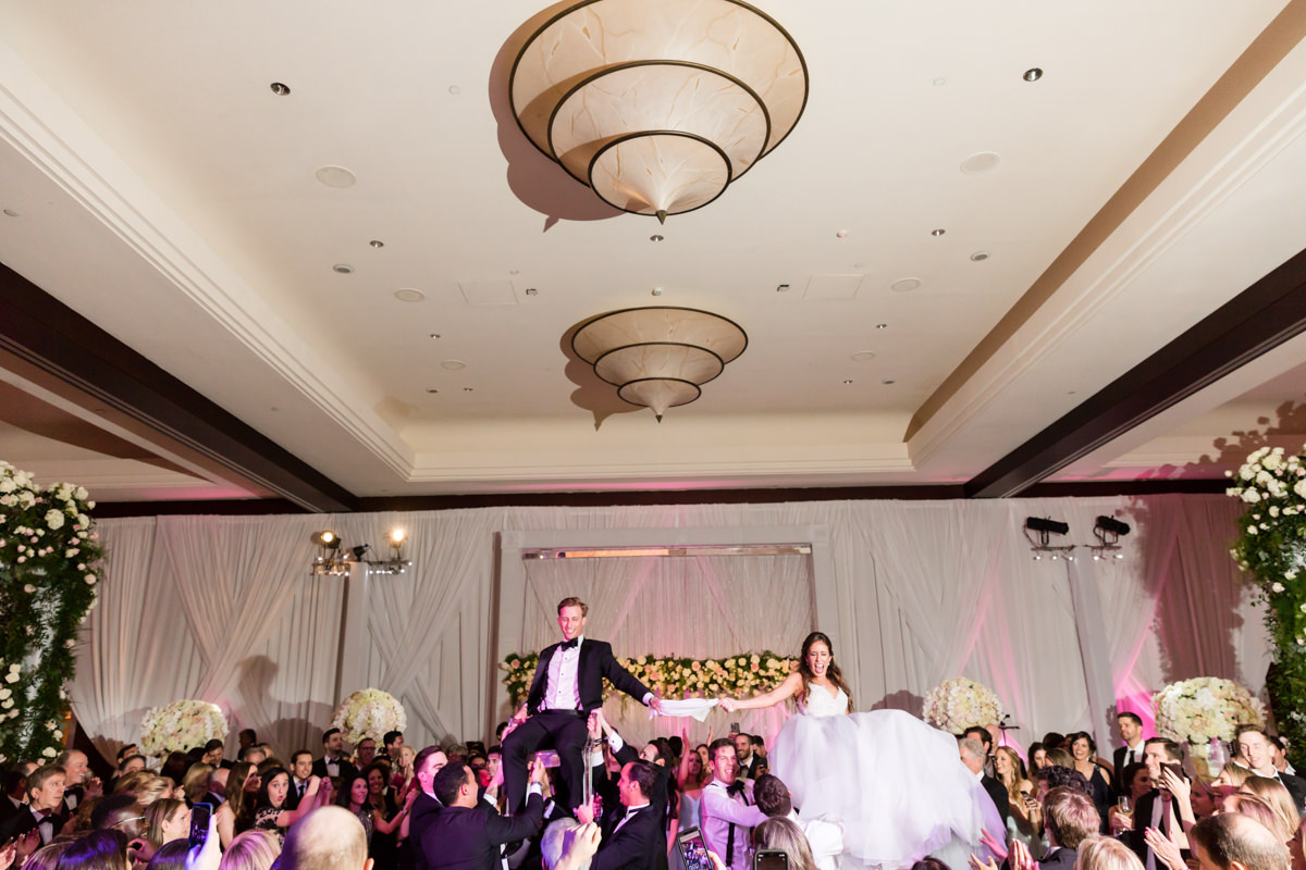 Bride and groom are lifted in chairs during hora at their wedding Mandarin Oriental on Brickell Key.