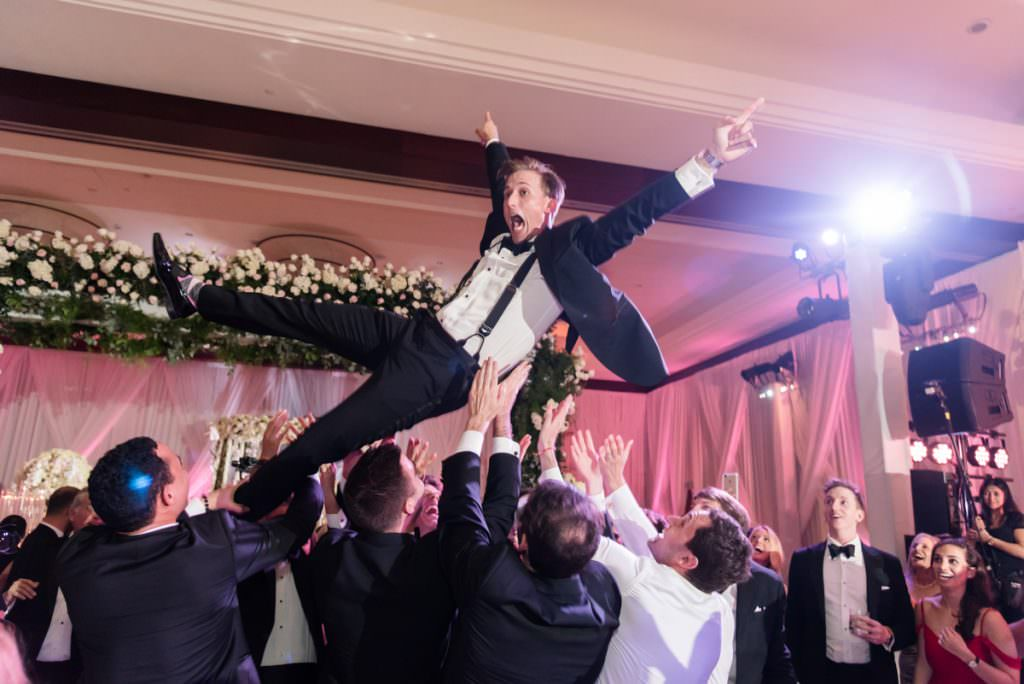 Groom being thrown in the air during a wedding reception