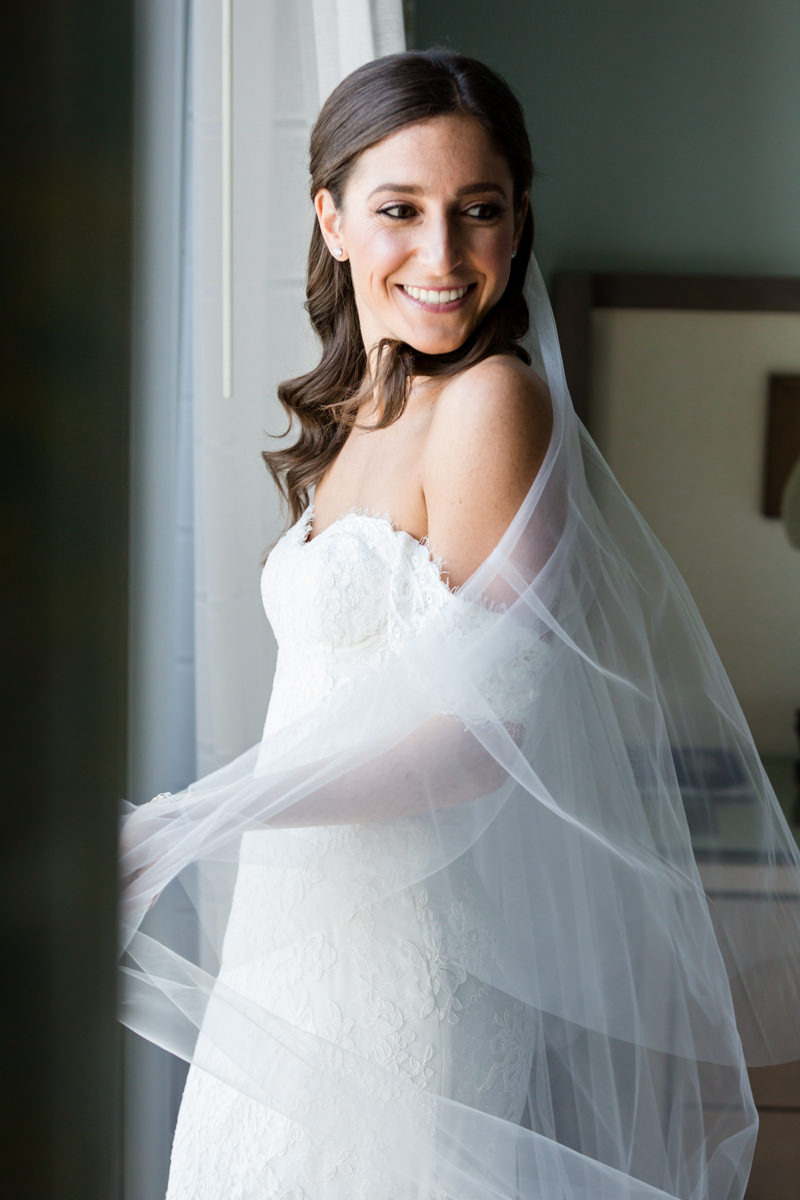 Bride smiling after putting on her veil in the bridal suite at the Ritz Carlton Key Biscayne.