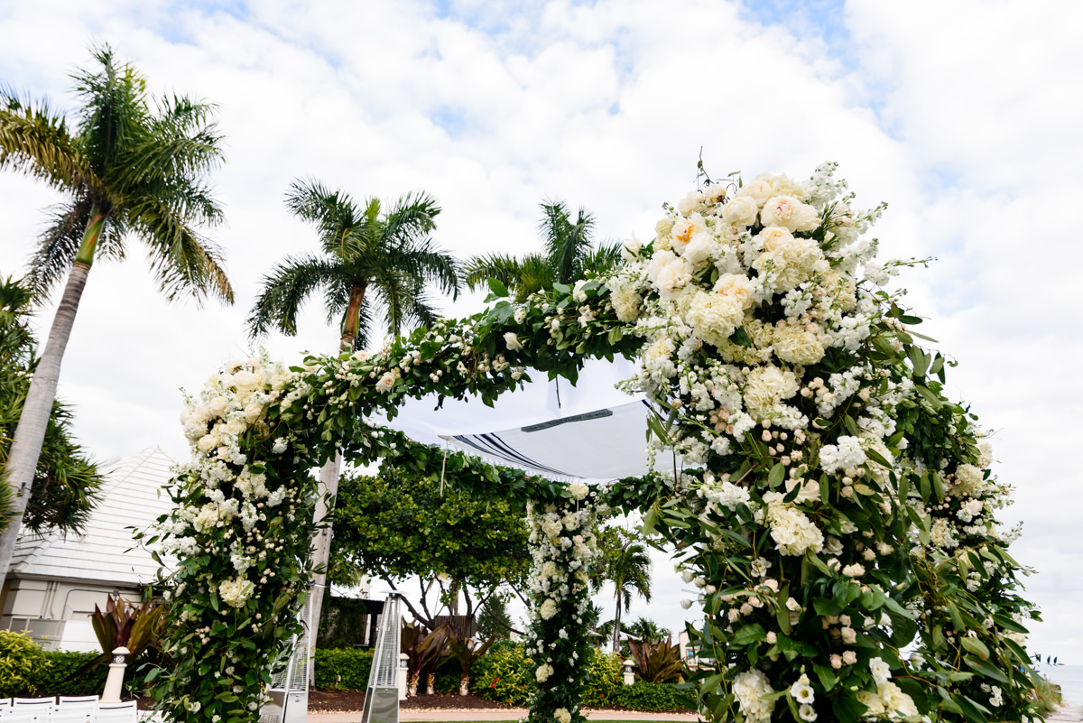 A white flower covered chuppah designed by Avante Gardens during a wedding at the Ritz Carlton on Key Biscayne.