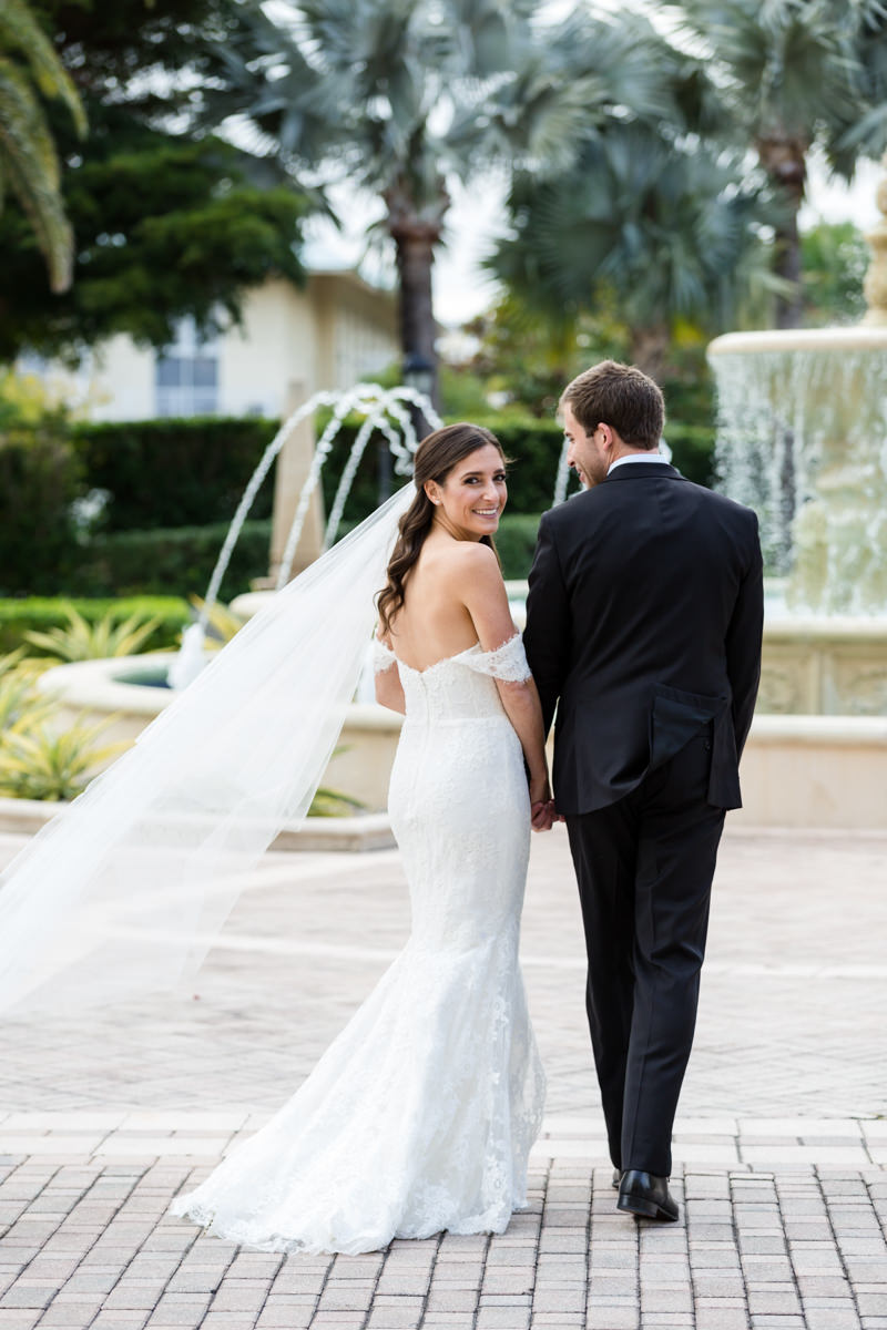 Bride and groom walking towards the fountain at the Ritz Carlton in Key Biscayne.