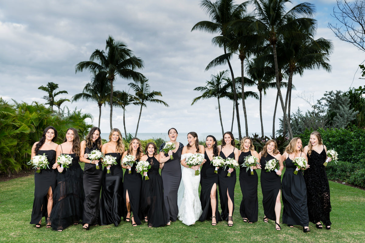Bridesmaids in black dresses walking together at the Ritz Carlton in Key Biscayne.