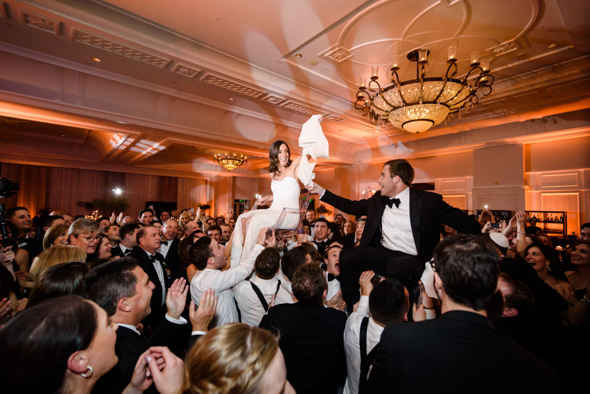 Bride and groom in chairs during the hora at the Ritz Carlton on Key Biscayne.