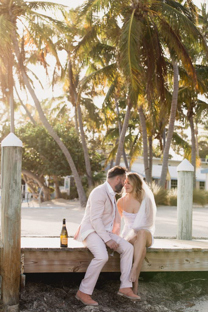 A bride and groom share a glass of champagne at the Pines and Palms Resort in the Florida Keys.