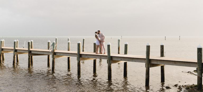 A groom, wearing sunglasses and pink suit, walks down the dock at the Pines and Palms Resort in Islamorada.