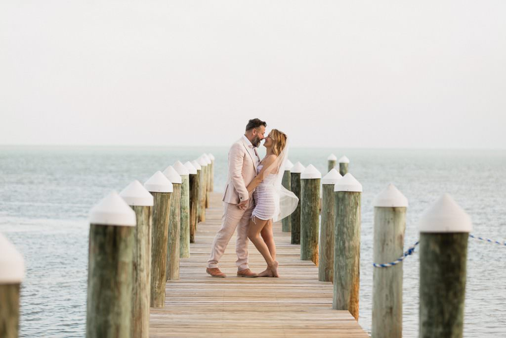 A couple kiss on the dock during their elopement in the Florida Keys.