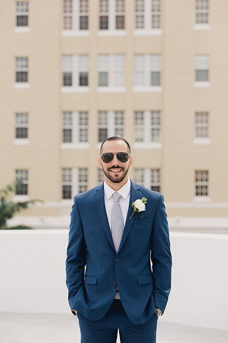 Groom poses for a portrait on the roof of the Miami Beach courthouse parking garage.