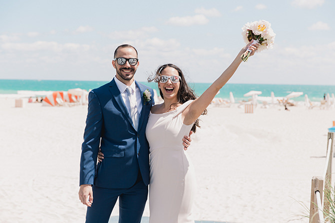 Couple smiling on Miami Beach after their elopement at city hall while wearing bride and groom sunglasses.