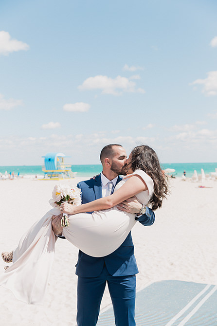 Couple kissing on the beach after their elopement at city hall.