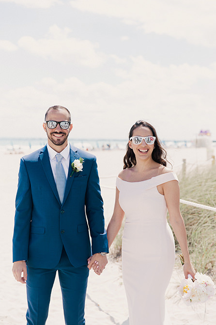 Couple poses for a portrait on the sand wearing bride and groom glasses.