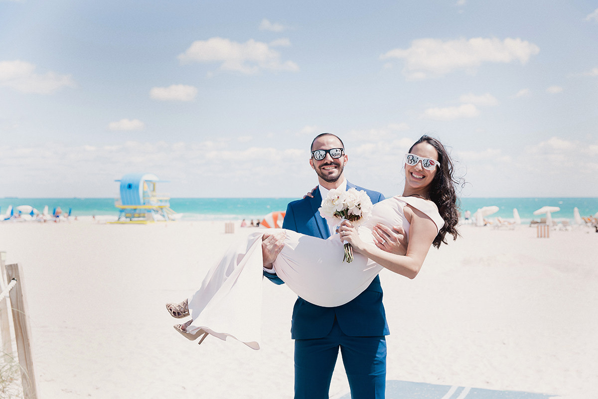 Groom carries bride off the beach after eloping at Miami Beach City Hall.