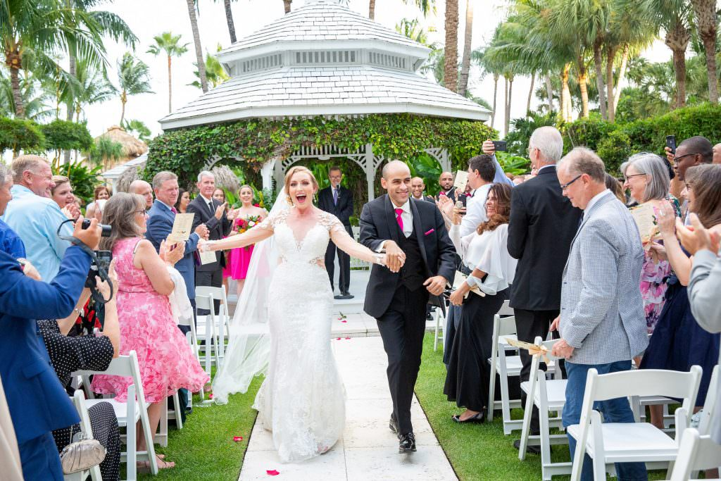 A couple walk down the aisle after their wedding ceremony at the Palms Hotel in Miami Beach.